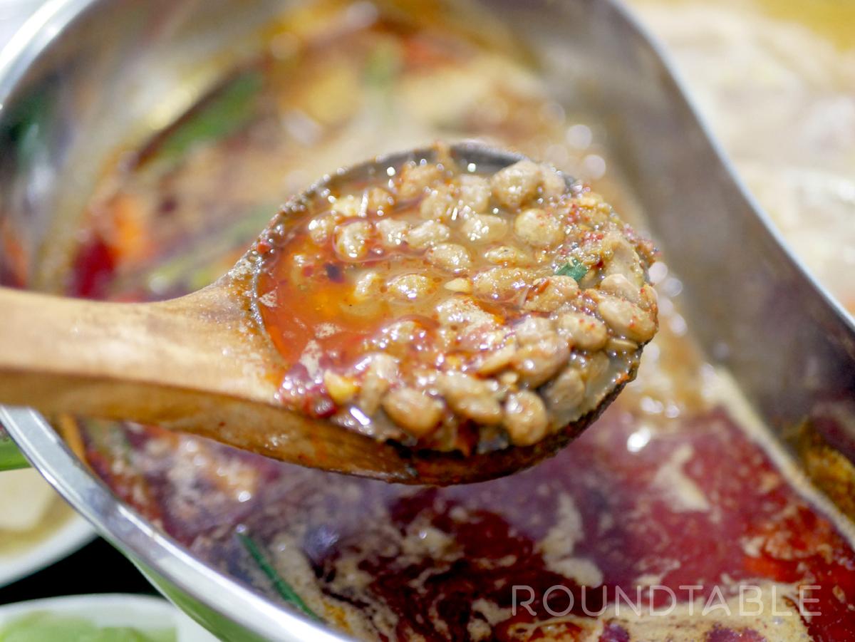 貴陽市内で何度か移転を重ねている「小两口豆豉油渣火鍋」の豆豉鍋。干豆豉を何種類かブレンドして作っており、さらりとしてコクがある。